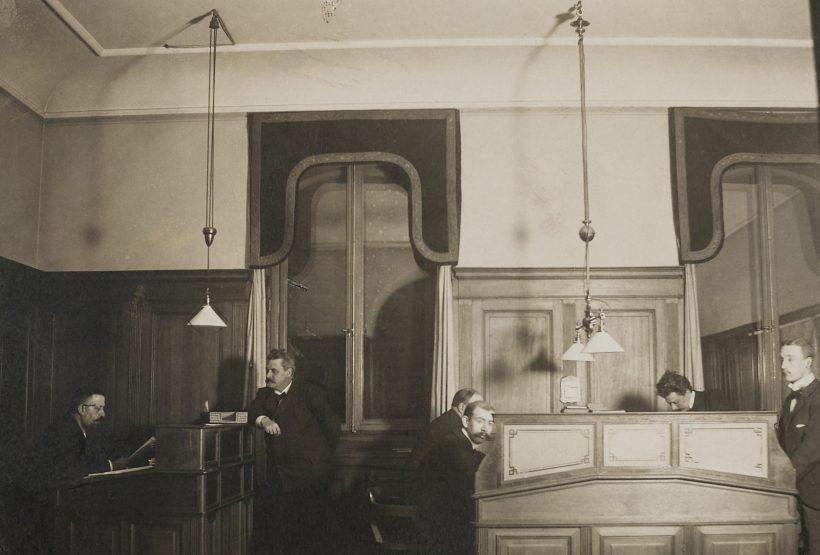 Bild av kontoret i Hallwylska palatset, från början av 1900-talet. Flera män står vid sina skrivbord.