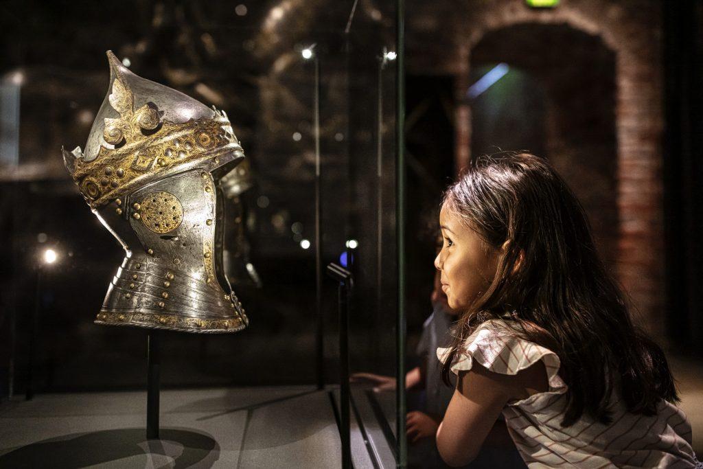 Barn som tittar nyfiket in i en museimonter på en hjälm från en rustning