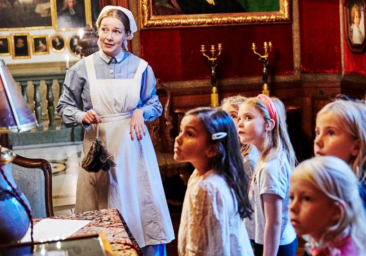 Guide som visar en barngrupp runt på Hallwylska museet