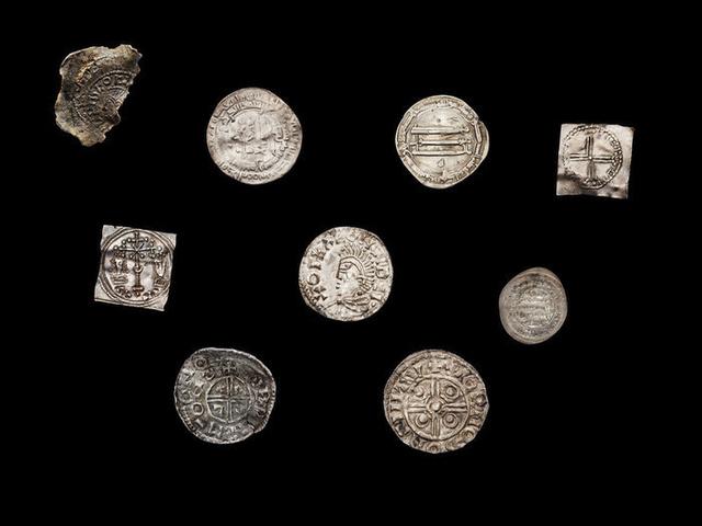 Silvriga mynt från vikingatiden mot svart bakgrund
